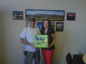 Leslie Quinn of Direct Communications presents Xbox drawing winner Terri Swallow of Idaho with his prize.
