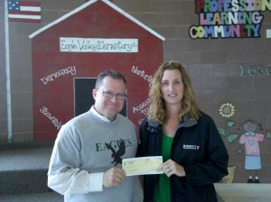 Diane Bradshaw of Direct Communications presents a donation to Eagle Valley Elementary in Eagle Mountain, Utah.