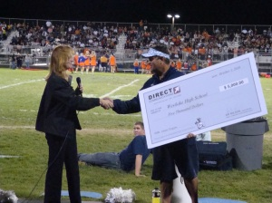 Diane Bradshaw, Direct Communications office manager for Eagle Mountain presents donation to Michael O'Connor, Athletic Director of Westlake High School.