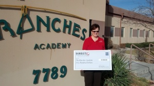 Mrs Payne of Ranches Academy with a check from Direct Communications.