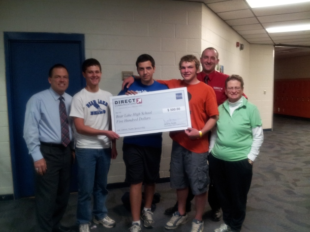 Daniel Parrish of Directcom presents a check for $500 to Bear Lake High Principal, Alan Schwab, and Athletic Director, Polly Dahlke, and student athletes.