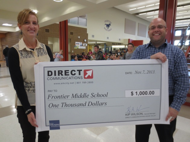 Diane Bradshaw of Direct Communications, presents Jeff Clark, School Counselor for Frontier Middle School , with a donation for $1000.