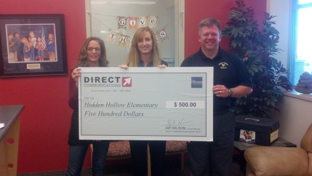Diane Bradshaw of Direct Communications presents a check for $500 to Tom Tillman, Principal of Hidden Hollow, and Reon Cowan, assistant.