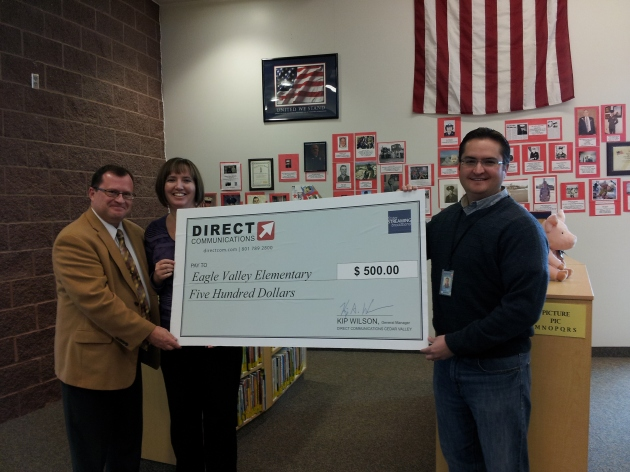 Ben Hayes, Account Executive for Directcom, presents a donation to Eagle Valley Elementary.