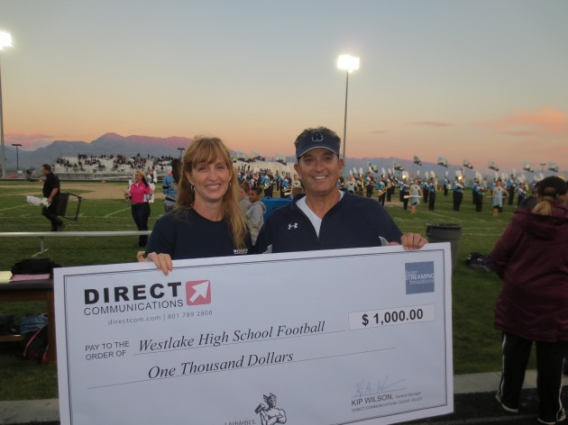 Diane Bradshaw, Community Relations Representative for Direct Communications presents a check to Westlake High School Football Head Coach Steve Clements.